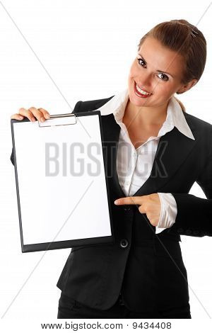 smiling modern business woman pointing finger on blank clipboard