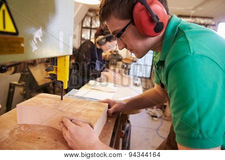 Shoemakers cutting and shaping wood to make shoe lasts