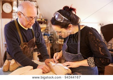 Senior shoemaker training apprentice to make shoe lasts