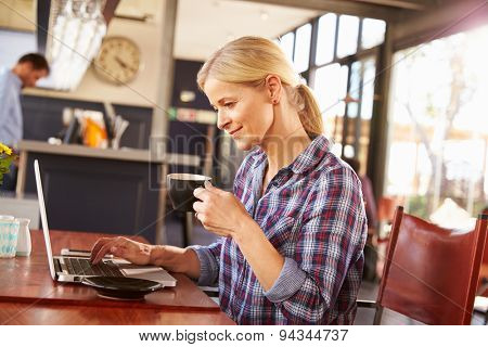 Woman using laptop computer at a coffee shop
