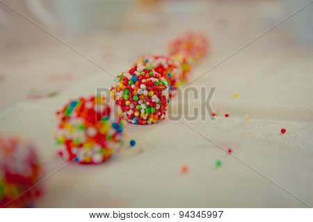 Close up on white chocolate balls covered with candies arranged in a row
