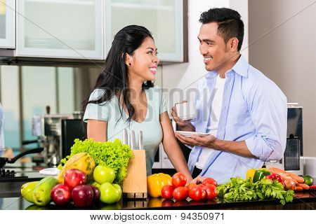 Asian couple, man and woman, cooking food together in kitchen and making coffee