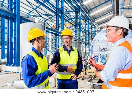 Asian factory worker and engineer as team inspecting a machine delivery