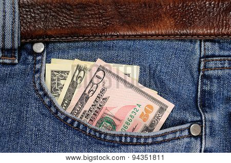 Several dollars banknotes seen from the pocket of jeans