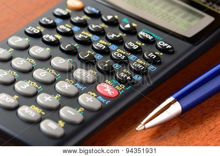 Calculator and pen on the table
