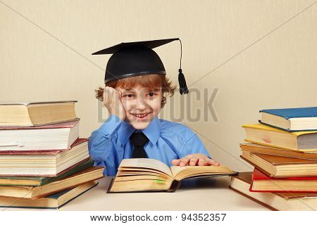 Little smiling boy in academic hat studies old books