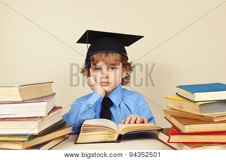 Little tired professor in academic hat studies old books