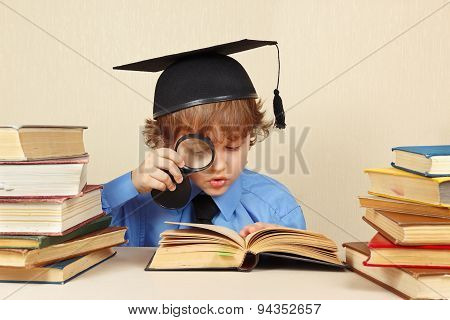 Little boy in academic hat studies an old books with magnifier