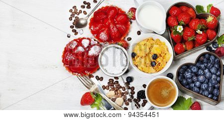 Breakfast with coffee, corn flakes, milk, tartlets and berry on wooden background