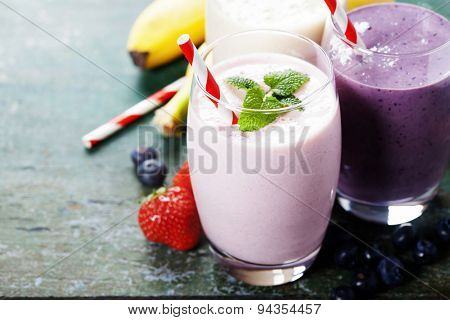 Fruit smoothies with black currant, strawberry and banana on wooden background