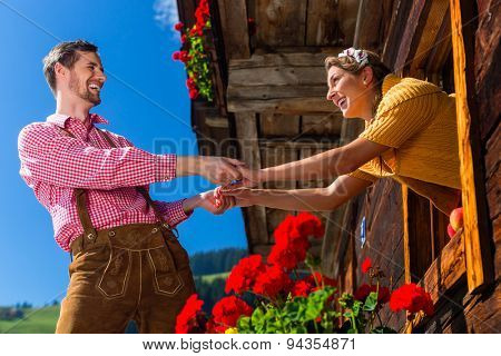 Couple in love at mountain hut window wearing traditional clothing