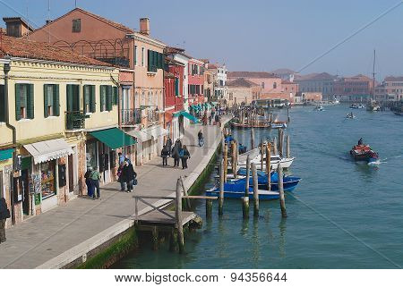 View to the Grand canal boats buildings and people at the street in early spring in Murano, Italy.
