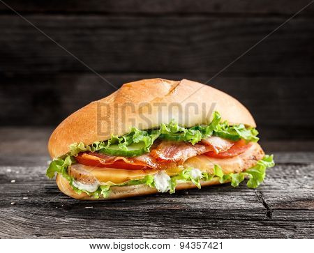 Sandwich with chicken, bacon cheese and vegetables