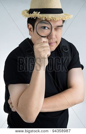 Portrait Of A Young Asian Man Looking Through A Magnifying Glass