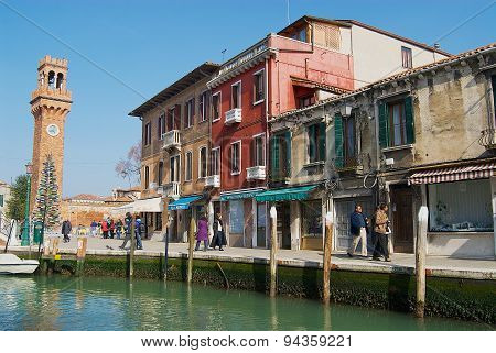 People walk by the street in Murano, Italy.