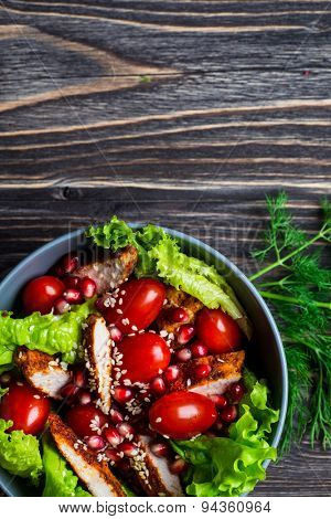 Chicken salad with tomatoes cherry, pomegranate and white sesame