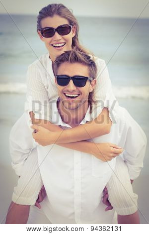 Handsome man giving piggy back to his girlfriend on the beach