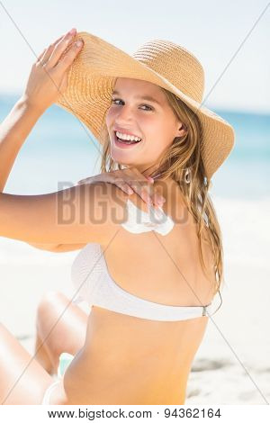 Pretty blonde woman spreading sun tan lotion on her shoulder at the beach