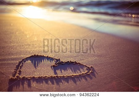 one heart drawn in the sand at the beach