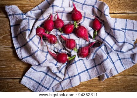 Red organic radishes on wooden rustic table