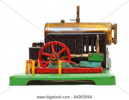 Steam engine. Vintage metal toy from 19th century. Object isolated on a white background.