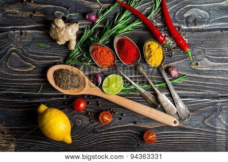 Spices. Herbs and spices selection in old metal spoons over wooden background. Rosemary, lemon and chili pepper.