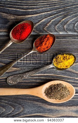 Spices. Herbs and spices selection in old metal spoons over wooden background. Curry, Saffron, turmeric, cinnamon and other.