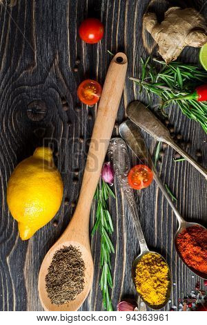 Spices. Herbs and spices selection in old metal spoons over wooden background. Rosemary, ginger and lemon.