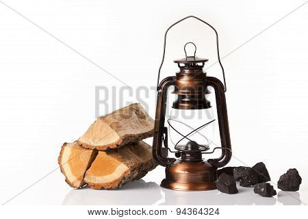 Pile of firewood, coal lumps  and oil lantern isolated on a white background