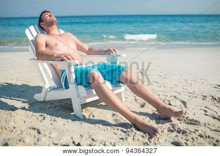 Man relaxing on deck chair at the beach on a sunny day