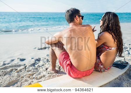 happy couple with surfboard on a sunny day at the beach