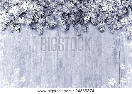 Snow-covered fir tree branch with decorations on wooden background