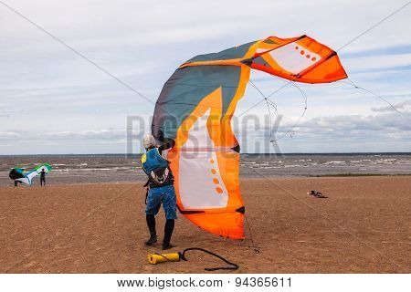 Kite Surfer Wearing A Wetsuit Is Preparing His Kite On A Windy Day