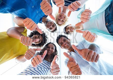 Creative team gesturing thumbs up while in circle