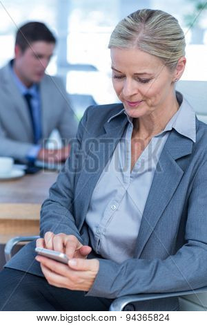 Businesswoman texting on her mobile phone with colleague in background in an office
