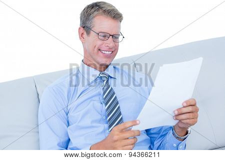 Focused businessman reading a document against a white wall