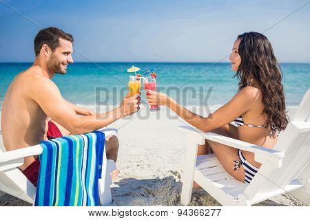 Happy couple drinking a cocktail together on a sunny day