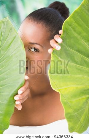 Portrait of a pretty woman looking through leaves on a greenness background