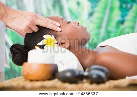 Side view of an attractive young woman receiving temple massage at spa center