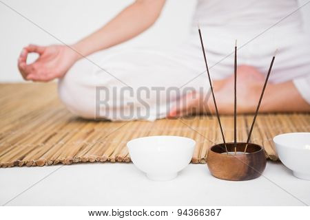 Fit woman meditating on bamboo mat on white background