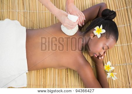 Upward view of a pretty woman enjoying a herbal compress massage at the health spa