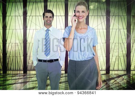 Businesswoman having phone call while her colleague posing against window overlooking city