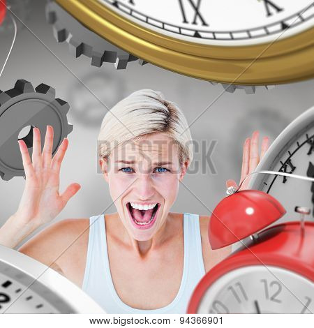 Angry blonde screaming with hands up against grey vignette