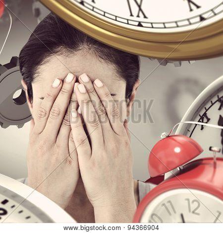 Sad woman hiding her face against grey vignette