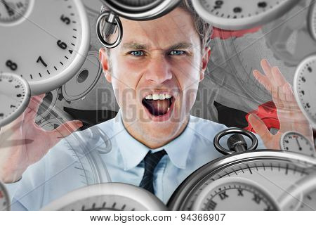 Angry businessman shouting against grey background