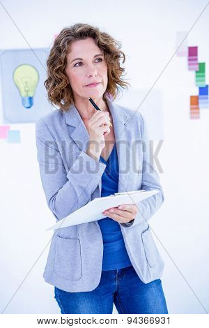 Thoughtful creative businesswoman looking away in office