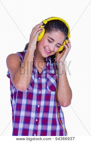 Pretty brunette listening music with headphone on white background