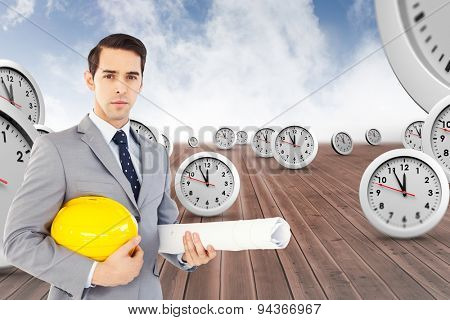 Serious architect holding plans and hard hat against cloudy sky background