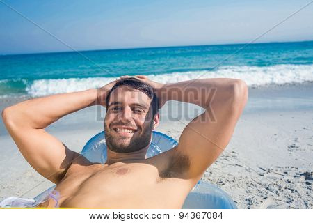 Handsome man lying on the beach looking at camera on a sunny day