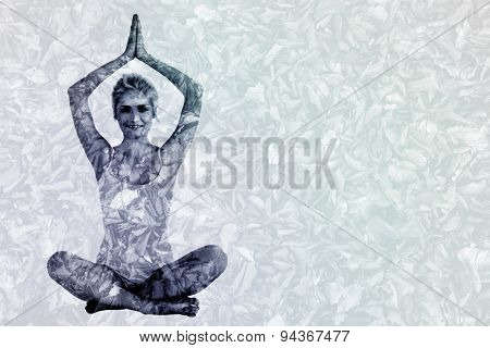 Toned young woman sitting with joined hands over head against detail shot of dry leaves